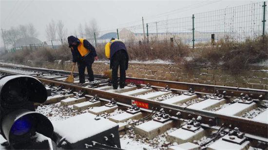在红旗设备7号道岔处进行扫雪除冰作业.-以雪为令保畅通图片