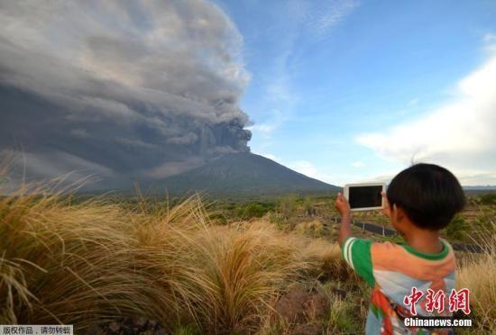 当地时间11月26日,印尼巴厘岛卡朗阿森,阿贡火山喷发。图为当地小朋友淡定拍照。   中新网11月26日电 据新加坡《联合早报》报道,当地时间11月25日,印度尼西亚巴厘岛的阿贡火山冒出大量浓烟,这已是本周的第二次。   当地时间11月26日,印尼巴厘岛卡朗阿森,阿贡火山喷发。   自今年8月起就一直处于活跃状态的阿贡火山,周二傍晚开始喷出大量灰色浓烟,高度达700米。   25日,法新社报道,印尼官方表示,当天喷发的浓烟最高可达1500米,这比周二(21日)喷发的高度高逾一倍。   《联合早报》26